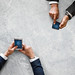 Business people syncing data by mobile phone