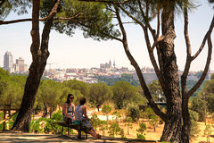 Watching the city pass by (Tony Shertila) Tags: esp geo:lat=4041969925 geo:lon=374849674 geotagged madrid moncloaaravaca spain europe park bench seat people talking chatting cityscape tree forest city buildings palace