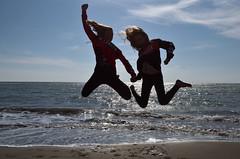 E via! Più veloci dell'alluce! (Il cantore) Tags: due two ragazze girls salto jump spiaggia beach schore sabbia sand acqua water mare sea cielo sky nuvole clouds controluce backlit silhouette onde waves