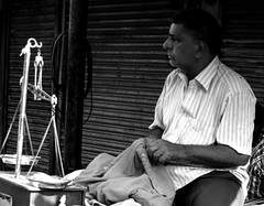 Weighing his options (magiceye) Tags: salesman street streetphoto streetportrait fleamarket mumbai bnw india monochrome blackandwhite