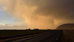 Mysterioso  (Iceland) (Harald Philipp) Tags: skógafoss iceland clouds rain sunset twilight dyrhólaós estuary mysterious dark forbidding dramatic sky orange silhouette houses car headlights road volcanic hills bluffs weather storm rainstorm nikon d810