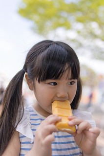 Little girl eating ice-cream in public park