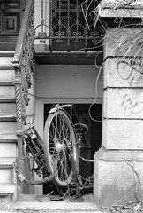 Bicycle parking in Amsterdam: dumped (onemanifest) Tags: amsterdam bicycles parking mess film analog monochrome blackwhite minoltaxd7 minoltamd50mm117 ilfordxp2 dumped stairwell banister