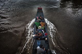 Fishermen traveling on the black water of Mekong delta