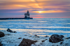 A Distant Hope (PopsDigital) Tags: lighthouse pier harbor kewaunee wi wisconsin sunrise earlymorning morning early dawn landscape lakemichigan water lake sun clouds orange red snow cold winter ice rocks shore freezing frozen billpevlor popsdigital color colour waves sky light kewauneecounty doorcounty horizontal horizon sonyslta77v