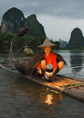 Cormorant Fisherman at Yangshuo in China (mlloyd4075) Tags: fisherman china cormorant fishing yangshou sunset red river lamplight