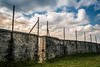 gefangen (DaveGassmann) Tags: mauer gefängnis draht wolken cloud blue green wall tor türe schloss steine