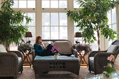 Young redheaded woman relaxes on loveseat in bright sunroom read (blurMEDIA Stock) Tags: saturday sunday adultlearning autumn book bookclub bright business businesswoman busy career casual continuingeducation cottage enjoyment entrepreneur female fiction glassceiling glasses holiday home homeoffice houseplant independent job learning leisure lifestyle loveseat mom mother motivated nonfiction nourishment novel office professional reading redhair redhead relaxation scarf selfimprovement sunroom sweater telecommute vacation weekend wicker window woman work workfromhome working young youngprofessional