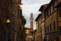 Convergencia... (encantadissima) Tags: siena toscana streetphotography vicolo case bandiere torre architettura tetti lampioni