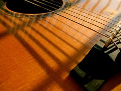 Morning Guitar (O Caritas) Tags: guitar reflections bridge saddle soundhole wood grain dust strings intersections shadow