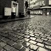 Street (Bernhardt Franz) Tags: street cobblestone kopfsteinpflaster man umbrella schirm rainy wet regnerisch blackandwhite bw buildings facades showcase bin verteilerkasten