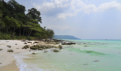 Where the jungle meets the sea (ORIONSM) Tags: kohrong beach cambodia jungle rocks sea ocean shore landscape blue sky clouds asia trees olympus omdem1 olympus14150mm