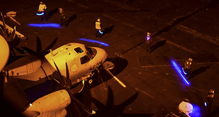 Sailors form a safety boundary around an E-2C on the flight deck.
