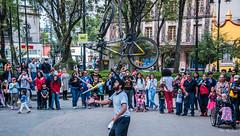 2018 - Mexico City - Coyoacan's Plaza Jardin Hidalgo (Ted's photos - Returns late June) Tags: 2018 cdmx coyoacan cropped mexico mexicocity nikon nikond750 nikonfx tedmcgrath tedsphotos tedsphotosmexico vignetting plazajardinhidalgo coyoacanplazajardinhidalgo plazajardinhidalgocoyoacan busker bike bicycle crowd denim denimjeans red redrule plaza kiosk wheels wheelchair people peopleandpaths strollerball capparkin parkwifizone wifi