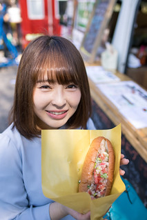 Young woman holding hot dog in front of food truck