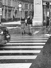 Yes It Is Snowing (tcees) Tags: bajcsyzsilinszkyway budapest hungary pest x100 fujifilm finepix bw mono monochrome blackandwhite sidewalk pavement crossing traffic buildings streetphotography street urban road roadsign people pedestrians man woman snow snowing