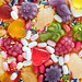 Flatlay of assorted jelly fruits and sprinkles textured background