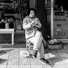 Spider woman (Go-tea 郭天) Tags: hangzhoushi zhejiangsheng chine cn hangzhou linan lady old woman knit knitting sleeping clothes pajama busy candid portrait alone lonely niddles sewing thread lines cold warm hot sun sunny shadow street urban city outside outdoor people bw bnw black white blackwhite blackandwhite monochrome naturallight natural light asia asian china chinese canon eos 100d 24mm prime life pavement shops plastic bag sidewalk