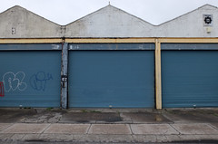 Shutters (sgreen757) Tags: avonmouth bristol fuji fujifilm observations street photography portview road garages shutter doors blue squares repitition run down despair dirty suburb village crap