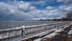 frozen fence (montrealmaggie) Tags: fence ice water sky clouds spring