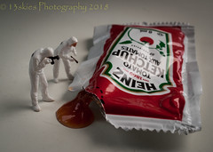 Oozing Out (13skies) Tags: ketchup pouch packet squeeze small modelrailroadfigures homodelrailroadfigures camera crimescene looking thinking figuring checking messy red sauce sonyalpha100 macroscopic macro tiny taste