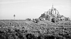 the road to mont st michel (khrawlings) Tags: france bw blackandwhite monochrome road sign montstmichel monastery church island grass normandy pilgrimage