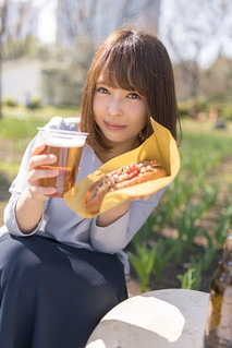 Young woman holding cup of beer and food for picnic