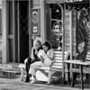 Chillin' Reykjavik girls (John Riper) Tags: johnriper street photography straatfotografie square vierkant bw black white zwartwit mono monochrome reykjavik iceland candid john riper xt1 fuji 18135 chilling girls beauties teens vape shop drekinn bench table sun glasses
