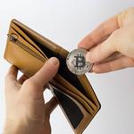 Man putting Bitcoin in his wallet thumbnail