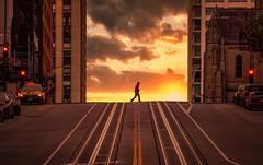 Sunwalker, San Francisco (reinaroundtheglobe) Tags: sanfrancisco california californiastreet streetphotography clouds sunrise sunset building cars 1person railtracks usa city
