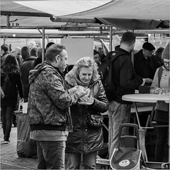 Bungling with a herring sandwich (John Riper - AWAY FOR AWHILE) Tags: johnriper street photography straatfotografie square vierkant bw black white zwartwit mono monochrome netherlands candid john riper rotterdam fuji fujifilm xt2 18135 market binnenrotte stall sandwich eating snacking couple zwvk