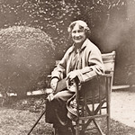 Eleanor Hull, full-length portrait seated in chair, in a garden with a book and a cane thumbnail