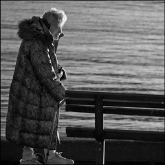 Finding her spot on the bench (HereInVancouver) Tags: elderlywoman whitehair cane wintercoat parkbench ocean water pacific englishbay candid streetphotography vancouverswestend bw blackandwhite vancouver bc canada canong3x framed lifeonaparkbench seawall ngc