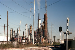1a-450 (ndpa / s. lundeen, archivist) Tags: nick dewolf nickdewolf photographbynickdewolf 1978 1970s color 35mm film 1a reel1a louisiana southernlouisiana neworleans refinery oilrefinery smokestack smokestacks tracks rail railroad railroadtracks traintracks crossing railroadcrossing traincrossing signal light smoke powerlines derrick