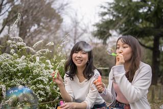 Young female friends blowing bubbles in public park