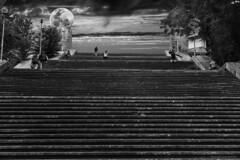 Stairway to heaven with my moon on a pedestal -  Escalera al cielo con mi luna sobre un pedestal (ricardocarmonafdez) Tags: ciudad city escaleras stairs arquitectura architecture cielo sky nubes clouds sunlight shadows contrast luna moon pedestal people peldaños steps monocromo monochrome blackandwhite bw bn 60d 1785isusm canon cityscape