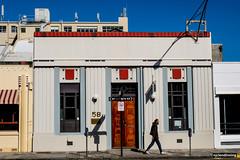 Art Deco Napier (smellerbee) Tags: napier hawkesbay nz newzealand eastcoast town person walking building bright colour autumn travel roadtrip road pavement sidewalk tennyson deadpan deadpanlook deadpanphotography