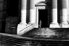 Exit of the angel (pascalcolin1) Tags: paris église church femme woman ange angel colonnes columns lumiere light ombres shadows porte door marches photoderue streetview urbanarte noiretblanc blackandwhite photopascalcolin 50mm canon canon50mm
