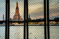 Temple of Dawn (Wat Arun) at Sunset (baddoguy) Tags: asia bangkok boundary buddhism capital cities chao phraya river city color image construction barrier copy space dawn dramatic sky dusk famous place fence grid horizontal igniting international landmark local mesh textile metal multi colored national no people outdoors pagoda photography religion spirituality steel stupa sunset surrounding wall temple building thai culture thailand travel destinations twilight unusual angle feature wat arun water window wire