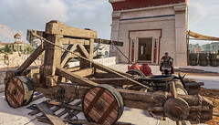 Caesar approaches an onager artillery piece placed in the fortifications of the Pharos in ancient Alexandria in Assassin's Creed Origins Discovery Tour (mharrsch) Tags: ancient alexandria egypt ptolemaicperiod assassinscreedorigins discoverytour mharrsch catapult artillery onager roman