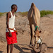 A somali man with a new born baby camel on his back, Awdal region, Lughaya, Somaliland