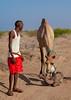 A somali man with a new born baby camel on his back, Awdal region, Lughaya, Somaliland (Eric Lafforgue) Tags: africa africanethnicity animal awdal camel developingcountry domestic domesticated dromedary eastafrica fulllength herbivorous hornofafrica livestock lughaya mammal man men mother muslim newborn oneadultonly onemanonly oneperson outdoors ruralscene soma6581 somalia somaliland vertical awdalregion
