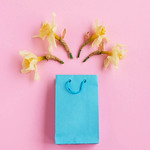 Flat lay of blue gift box and yellow spring flowers. Pink background. thumbnail