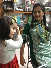 Esme putting on clips while Simi watches (olive witch) Tags: 2017 abeerhoque bangladesh bd dec17 december dhaka fem indoors kid night pair