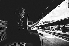 sitting, waitig, reading (matthias hämmerly) Tags: zürich zuerich switzerland candid street streetphotography shadow contrast grain ricoh gr black white bw monochrom monochrome city town urban station bahnhof bnw people dancing lonely blackandwhite einfarbig train man dark rails men personen zug
