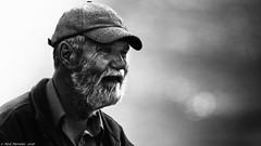 Life at the waters edge (Neil. Moralee) Tags: beerdevonneilmoraleesigma150500 neilmoralee fisherman fishing sea ocean man mature old beard harsh gritty heritage fleet uk britain england face portrait grainy black white mono bw bandw blackandwhite hat weatherbeaten beaten weather community bokeh light shimmer neil moralee nikon d7200 sigma 150500 telephoto candid