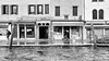 Cannaregio (Francis Mansell) Tags: canal water ripple venice reflection building restaurant kosher gamgam alley shop shopfront storefront window architecture post monochrome blackwhite quay hightide acquaalta pharmacy canaledicannaregio shutters passerby people cannaregio