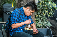 2018 - Mexico City - Condesa - Lunch Call (Ted's photos - For Me & You) Tags: 2018 cdmx cityofmexico cropped mexico mexicocity nikon nikond750 nikonfx tedmcgrath tedsphotos tedsphotosmexico vignetting cellphone boy male lad food eating blue blueshirt plaidshirt denim denimjeans fork takeout takeaway backpack seated sitting