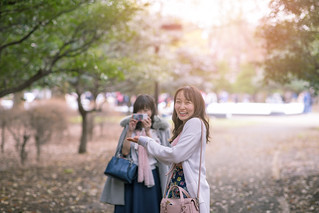 Happy female friends taking pictures in public park