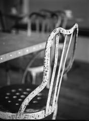 (steve aimone) Tags: cafechairs chairs table alchemy tea room tearoom alchemytearoom asheville northasheville northcarolina mamiya645pro mamiyasekor80mmf28 mamiyaprime primelens ilfordfp4 ilfordilfosol3developer 120 film 120film mediumformat monochrome monochromatic blackandwhite interior